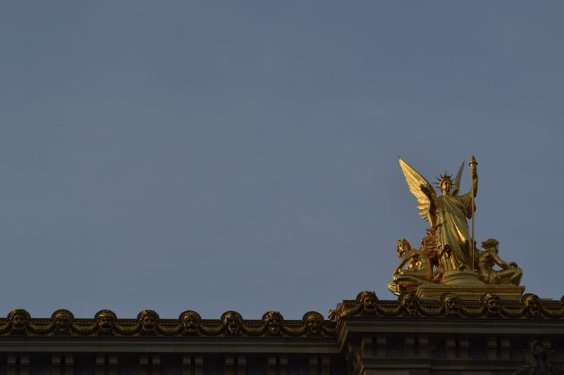 Low Angle View Of Angel Sculpture Against Clear Sky At Dusk