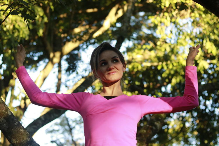 Low angle view of woman looking away with arms raised while standing against trees
