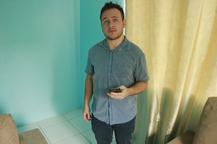 Blue Eyes One Person Standing Young Adult Young Men Front View Three Quarter Length Casual Clothing Indoors  Real People Lifestyles Leisure Activity Wall - Building Feature Home Interior Looking Technology Curtain Looking Away Men Contemplation