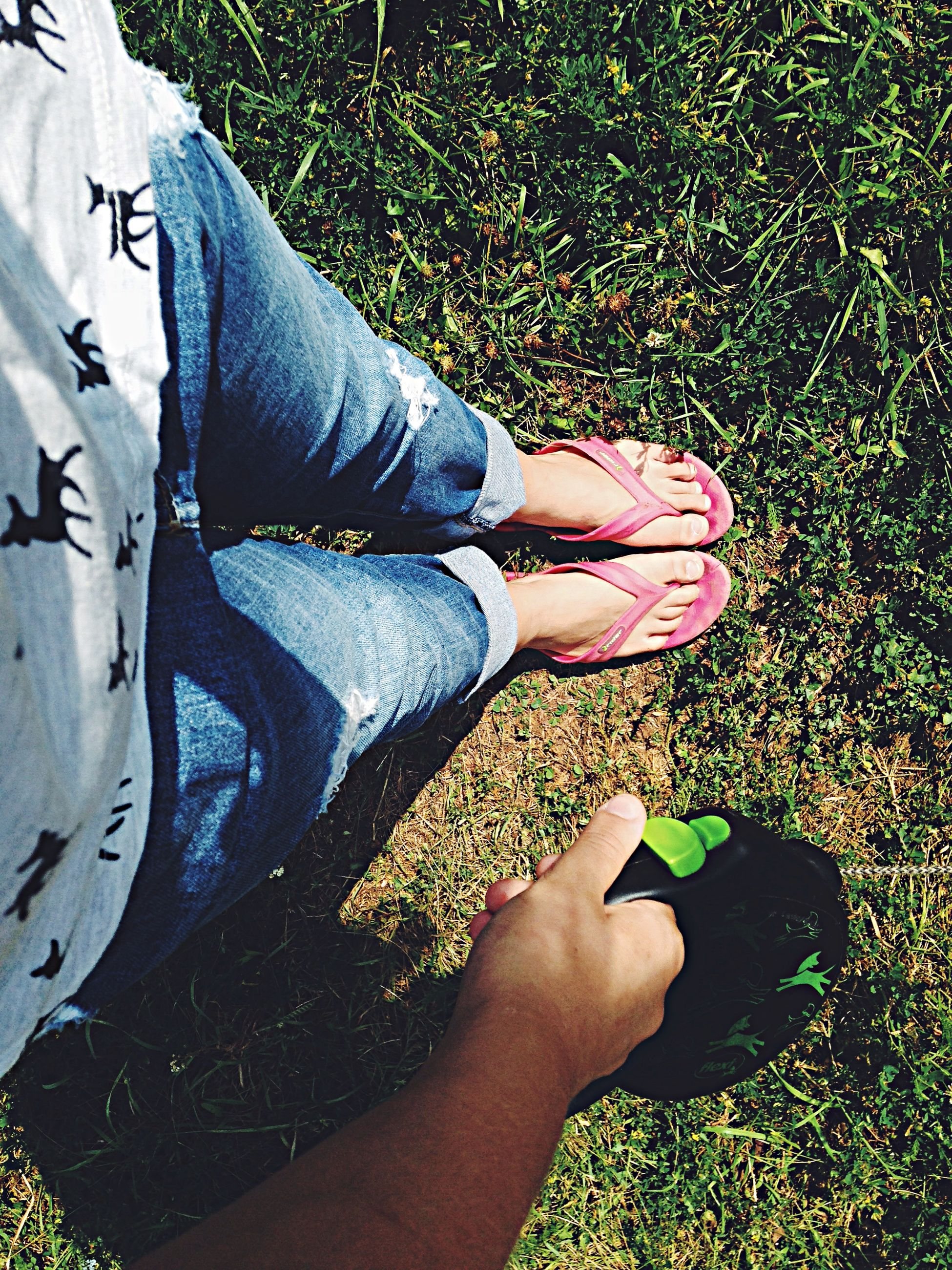 low section, person, lifestyles, leisure activity, shoe, personal perspective, casual clothing, standing, grass, high angle view, human foot, young women, footwear, barefoot, relaxation, legs crossed at ankle