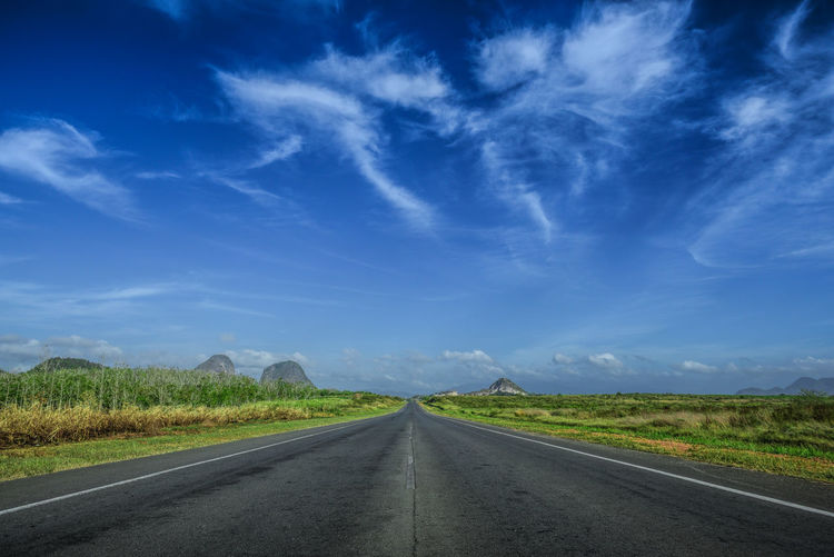 Surface level of country road against cloudy sky