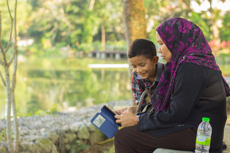 Mother and son using mobile phone while sitting in park