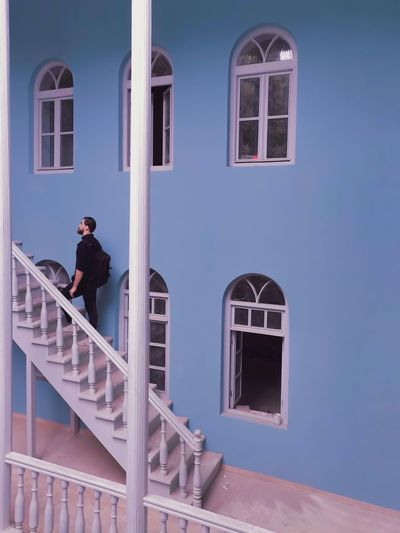Man standing by staircase against building