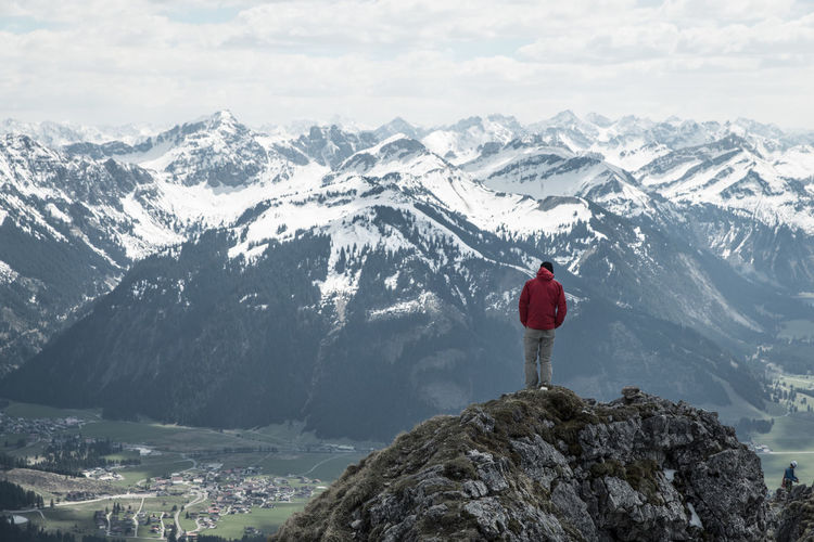 Rear view of man standing on cliff against european alps