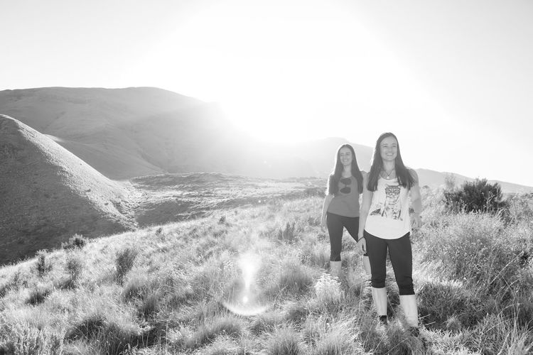 Smiling sisters standing on grassy field during sunny day