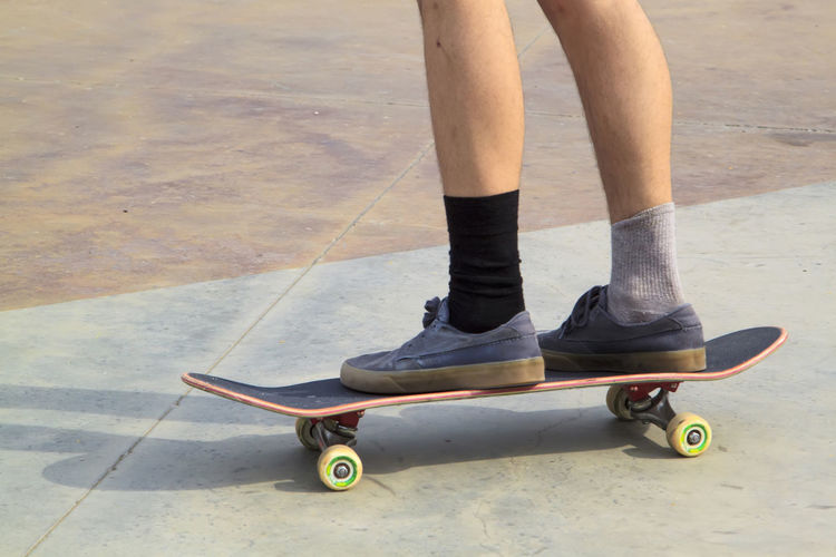 Low section of man skateboarding on footpath