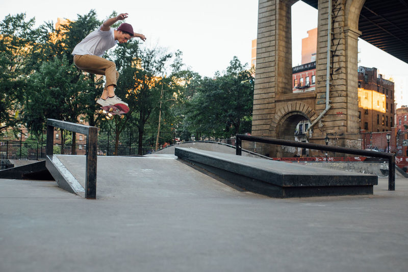 Man skateboarding in front of built structure
