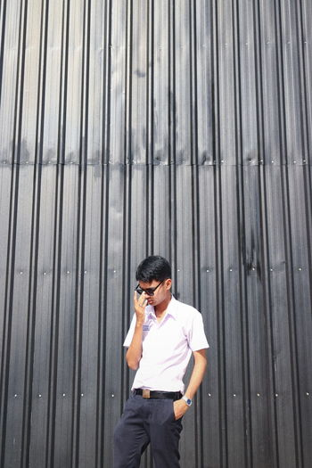 Young man standing against metal structure