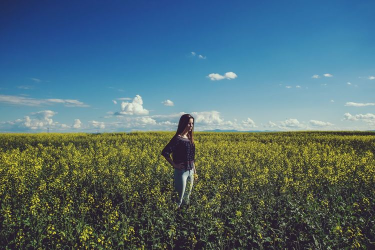 Woman standing on field against sky