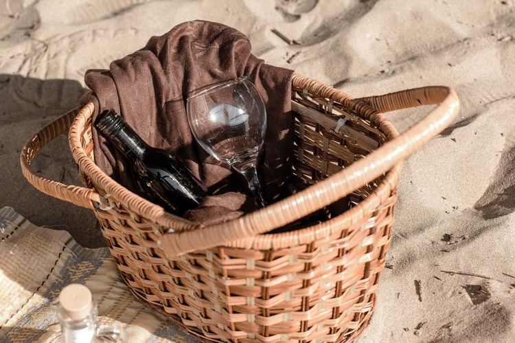 High Angle View Of Wine Bottle And Glass In Wicker Basket On Sand