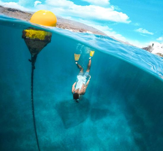 Rear View Of Snorkeling In Sea