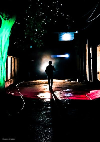Rear view of silhouette man standing on illuminated footpath