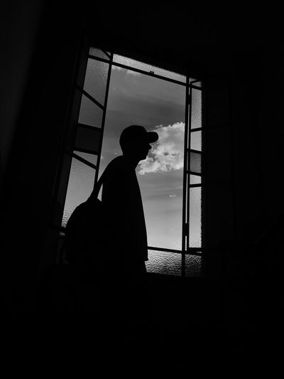 Side view of silhouette man standing by window