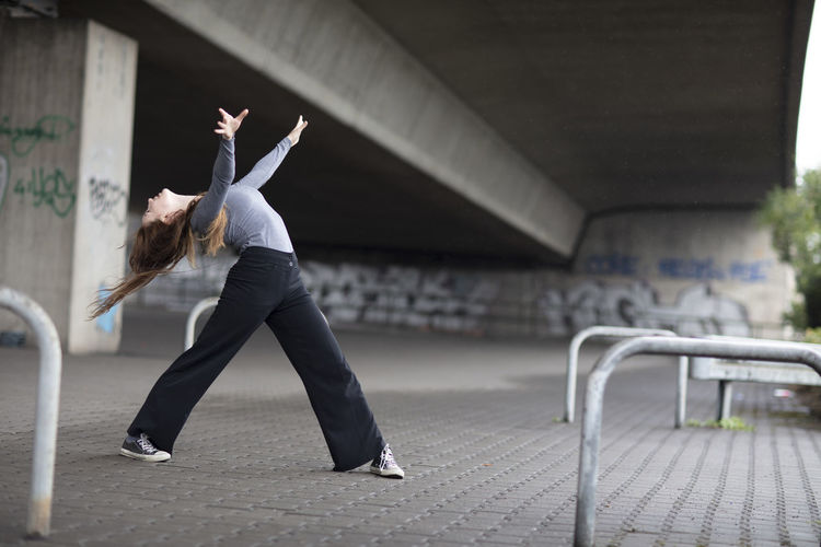 Young woman dancing under bridge