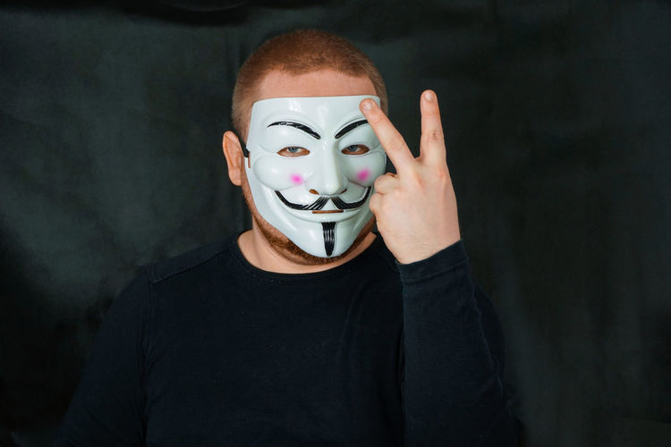 Portrait of man wearing mask while gesturing against black backdrop