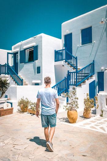Rear View Of Man Walking Against Buildings