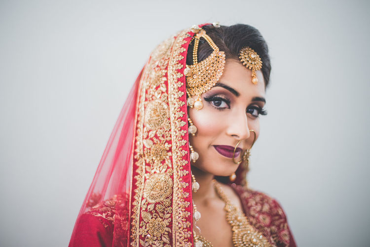 Portrait Of Beautiful Young Woman In Traditional Clothing Against White Background