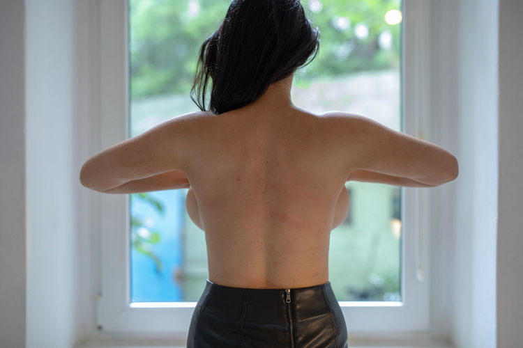 Rear view of shirtless seductive woman standing in front of window at home