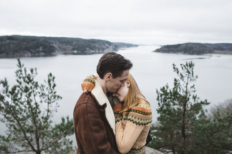 Couple kissing against sky during winter