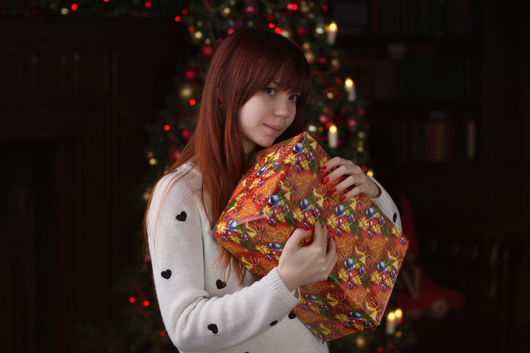 Portrait of young woman holding christmas present