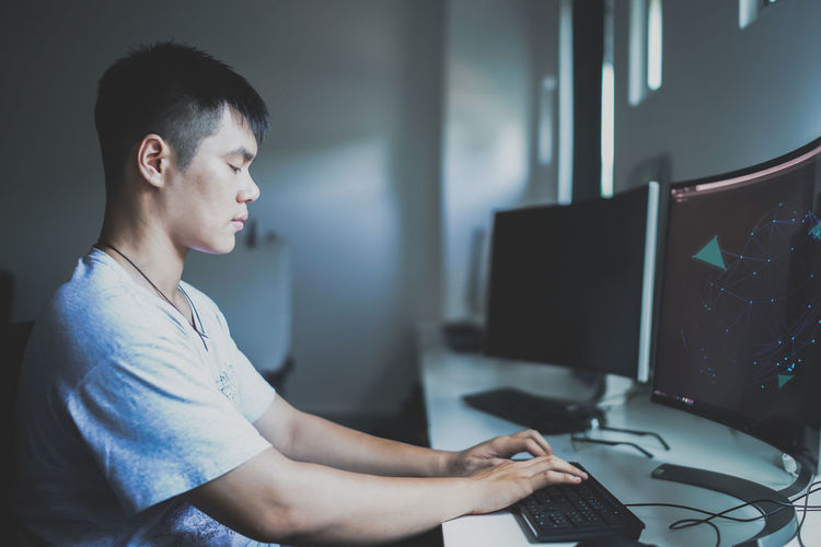 Side view of young man using computer while sitting on table