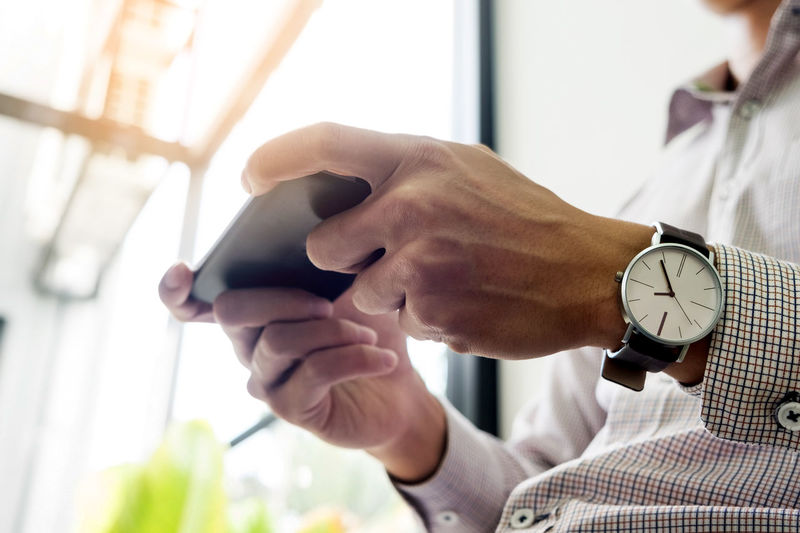 Midsection of man using mobile phone while sitting indoors