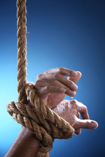 hand tied with rope Freedom Torture Blue Blue Background Body Part Close-up Colored Background Finger Focus On Foreground Hand Helpless Holding Human Body Part Human Hand Indoors  Leisure Activity Low Angle View One Person Rope Sky Strength Struggle Studio Shot Tied Tied Up