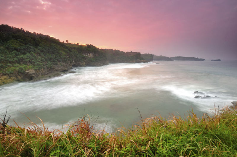 Sunrise at Klayar Beach, Pacitan, Yogjakarta, Indonesia INDONESIA Beach Beauty In Nature Day Fog Grass Horizon Over Water Landscape Nature No People Outdoors Power In Nature Scenics Sea Seascape Sky Sunset Tranquil Scene Tranquility Travel Destinations Tree Water Wave Yogjakarta