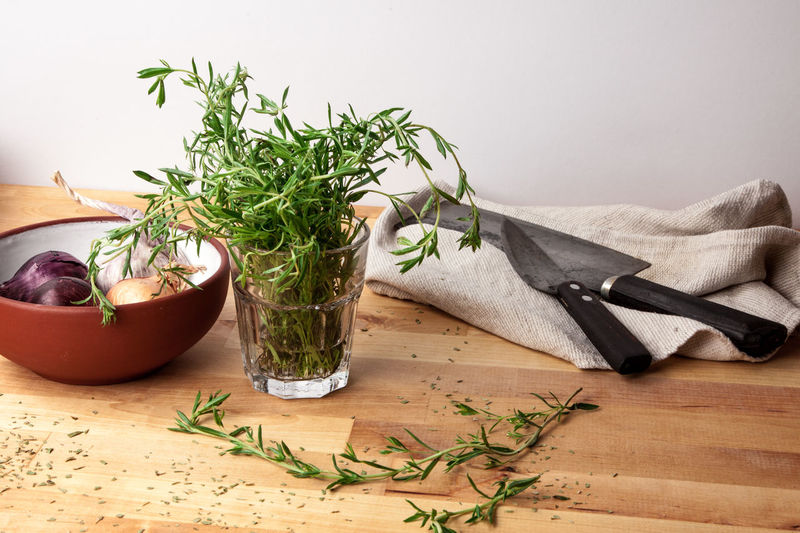 Rosemary with vegetables and knives on table