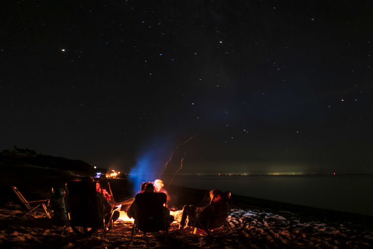 People sitting by fire against sky at night