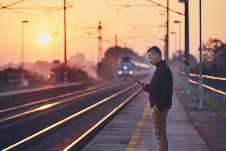 Young man waiting at railroad station platform and using smart phone against commuting train at sunrise. Man People Passenger Waiting Standing Real People Rail Transportation Railroad Track Railroad Station Railroad Station Platform Railway Train Sunrise Sun Sunset Moody Sky Sky Transportation One Person Lifestyles Using Phone Smart Phone Connection Communication Mobile Phone