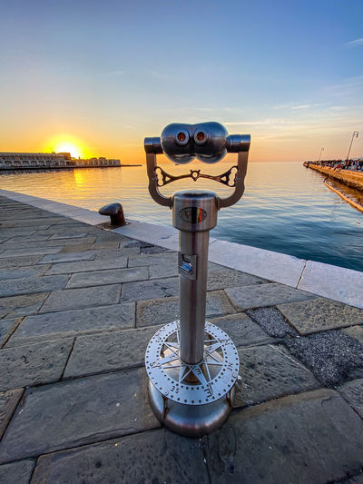 Coin-operated binoculars by sea against sky during sunset