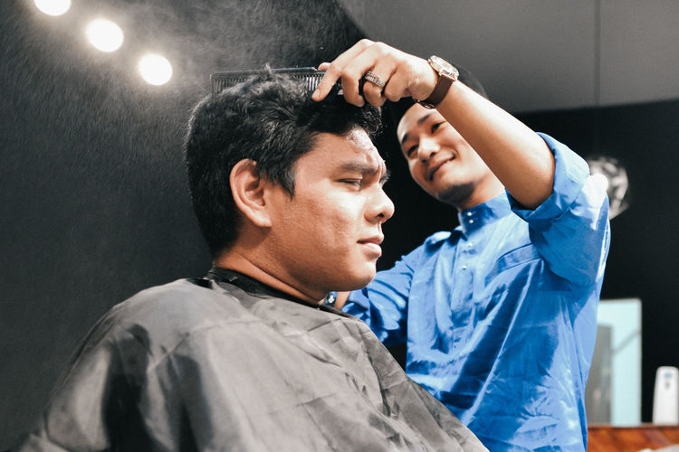 Hair dresser cutting hair of customer