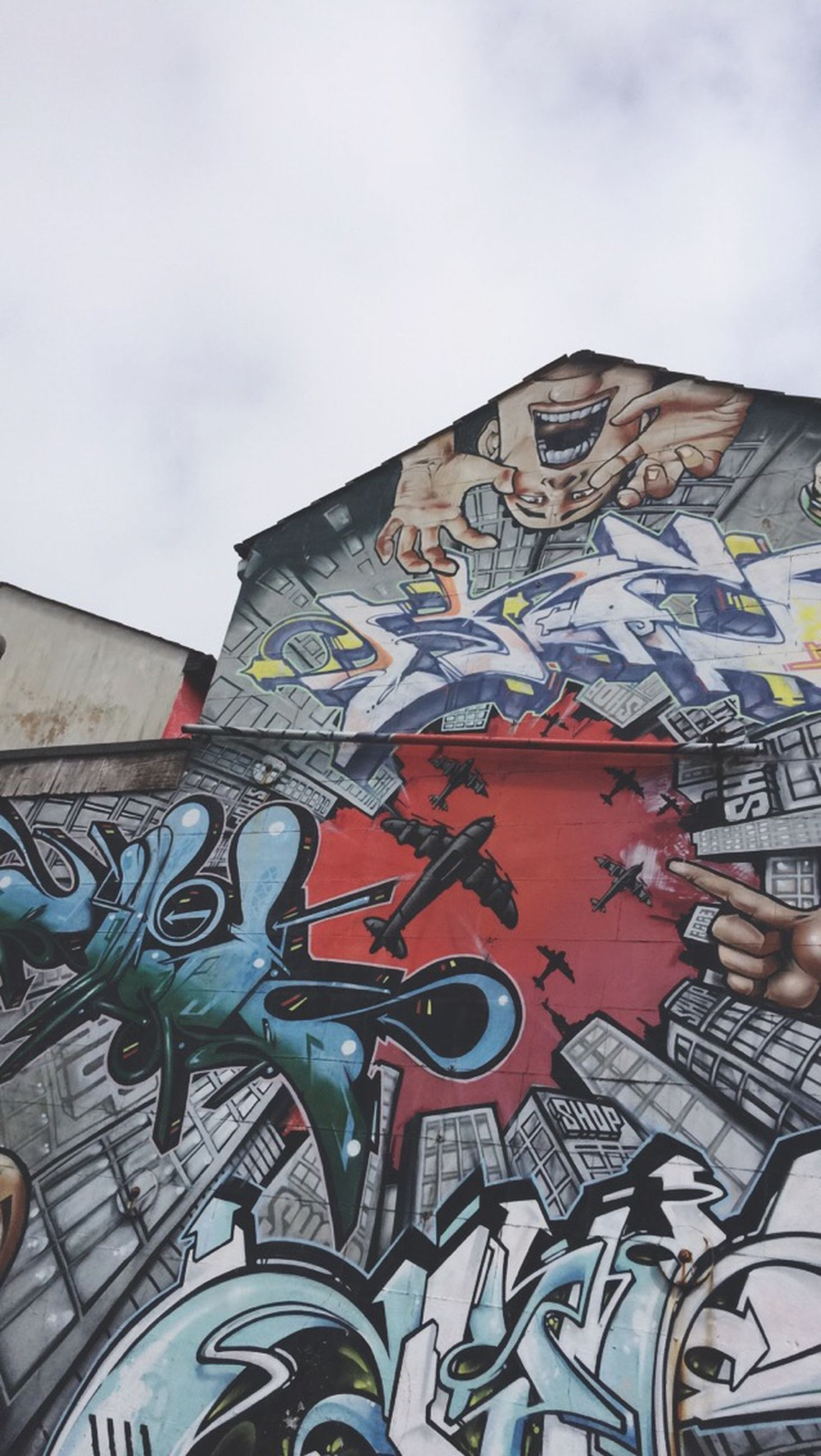 architecture, building exterior, built structure, graffiti, art and craft, art, creativity, low angle view, sky, wall - building feature, multi colored, day, building, outdoors, street art, design, cloud - sky, window, human representation, residential structure