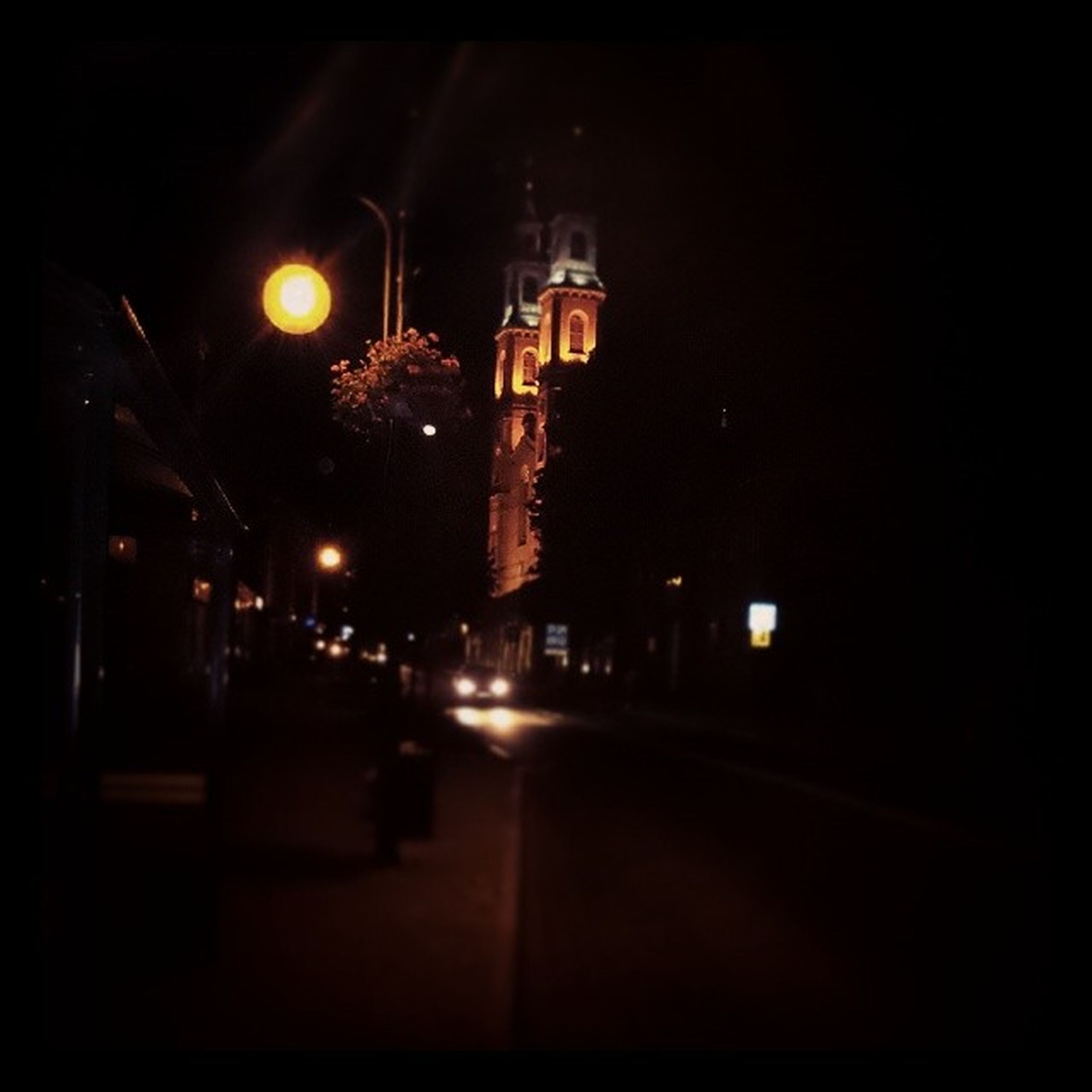 night, illuminated, building exterior, architecture, built structure, city, street light, street, tower, clear sky, lighting equipment, road, the way forward, sky, dark, outdoors, tall - high, clock tower, travel destinations, city life