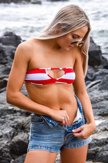 Young woman wearing hot pants at beach