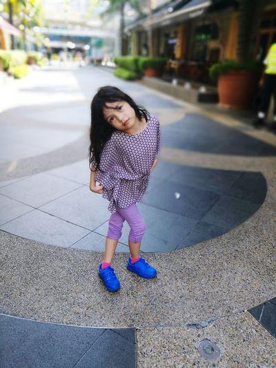 Portrait of cute girl standing with legs crossed at knee on street