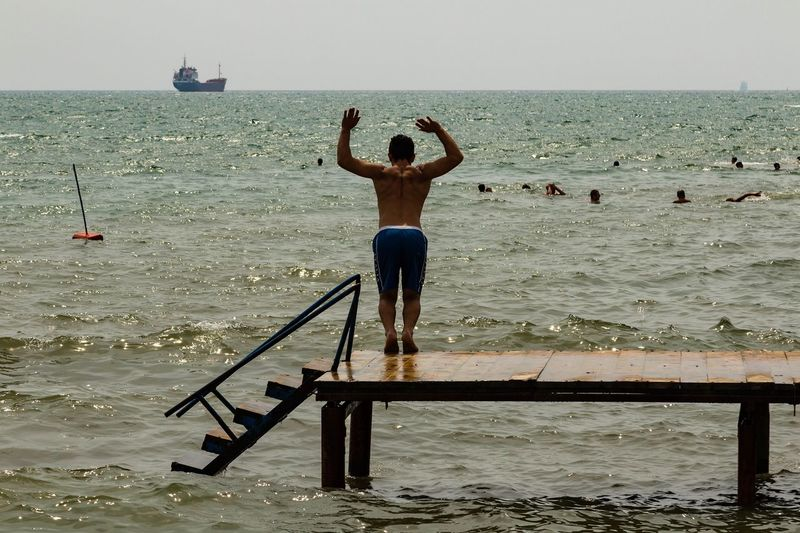 Rear view of shirtless man jumping into sea against sky