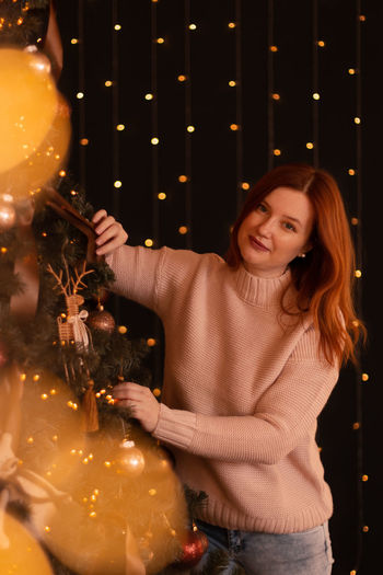 Young redhead woman decorating christmas tree at home above black wall with lights.