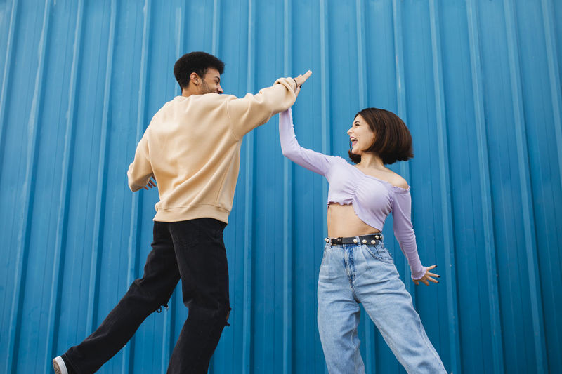 Side view of a young couple standing on blue wall
