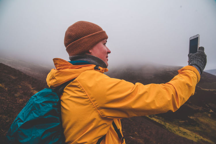 Side View Of Man Taking Selfie On Mountain