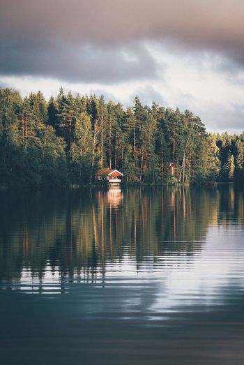 Mid distance view of cottage in lake against cloudy sky