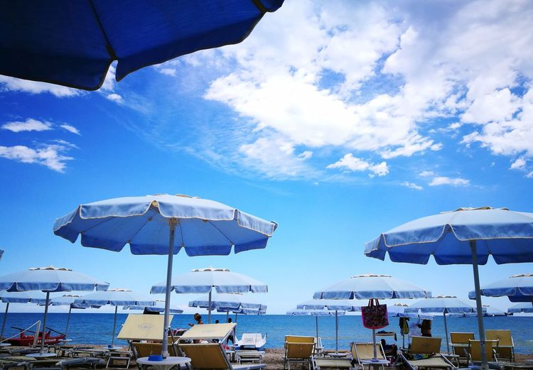 People on beach umbrellas against blue sky
