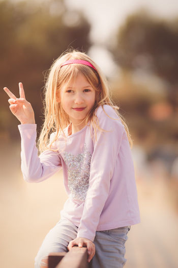 Portrait Of Girl Gesturing Peace Sign While Sitting On Railing