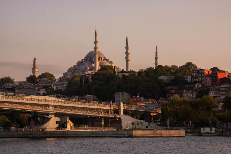Bridge by sea against historic mosque in city