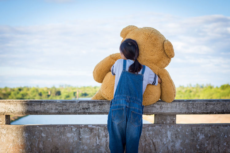 Rear View Of Woman With Teddy Bear Standing Against Sky