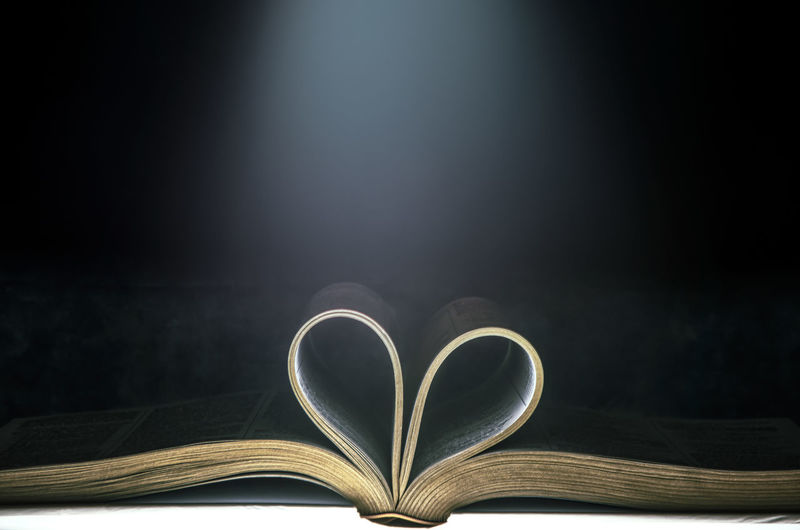 Close-up of heart shape on book against black background