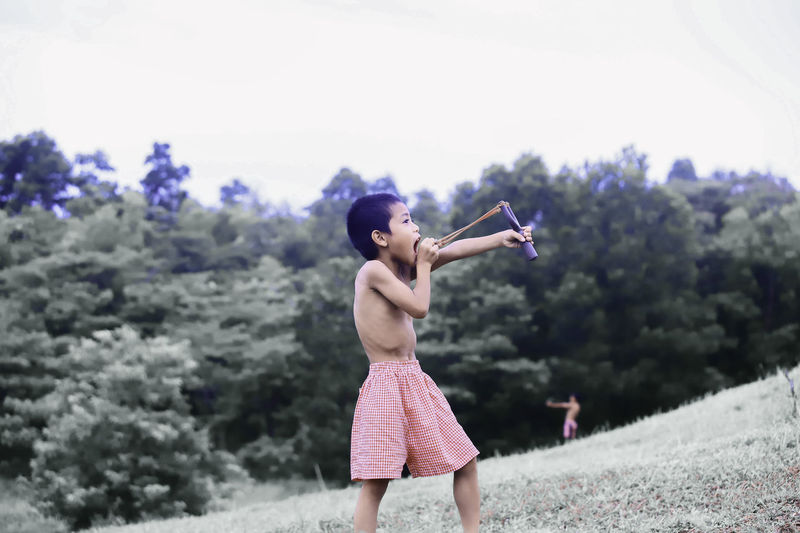 Shirtless boy aiming slingshot while standing on land against trees