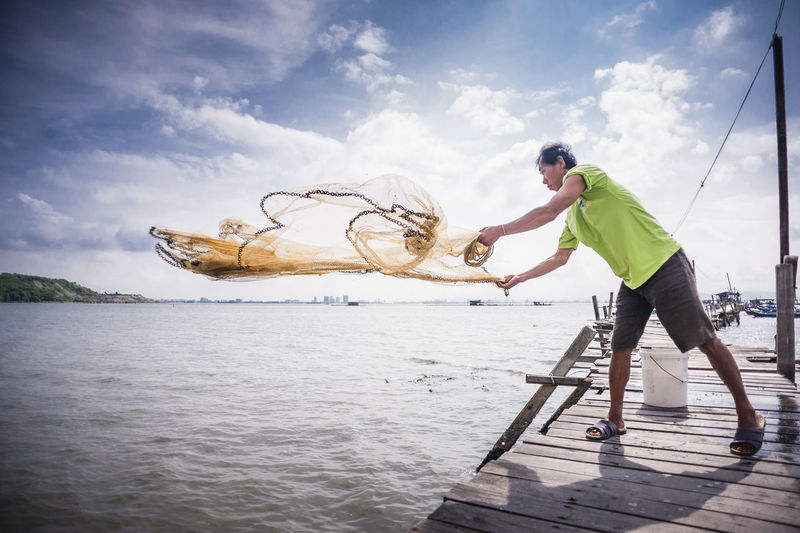 Casting Net Clouds And Sky Fisherman Fishing Fishing Net Outdoors People Sea Water Wooden Jetty