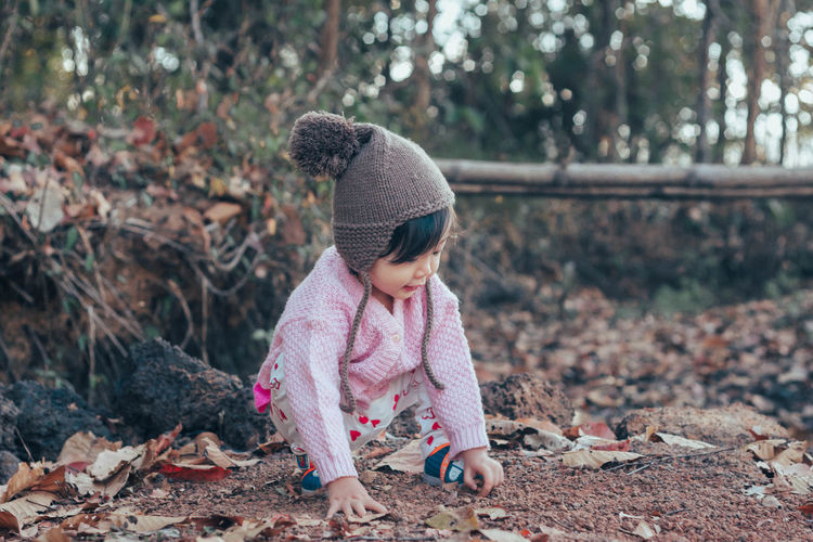 Cute baby girl crouching and playing with leaves during winter